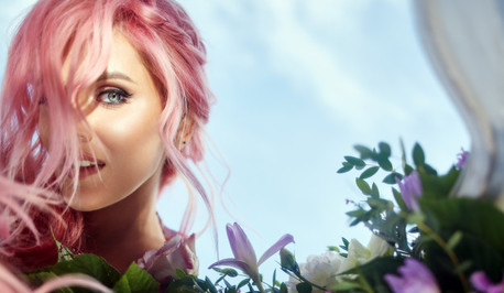 Beautiful woman with pink hair holds large bouquet with greenery and violet flowers 8353 1421
